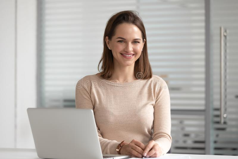 Head shot portrait of businesswoman sitting at office with laptop. stock images