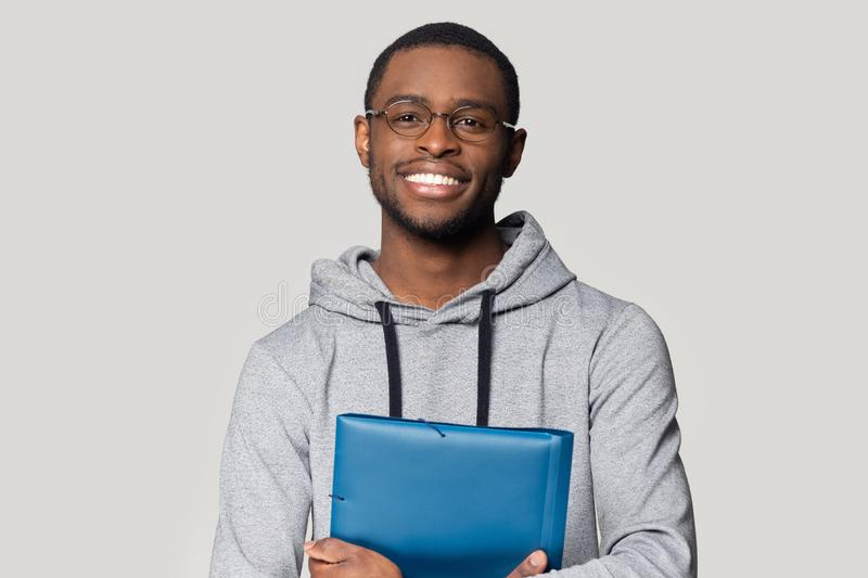 Head shot portrait smiling African American man holding folder. Head shot portrait smiling African American man in glasses holding folder for papers with stock photo
