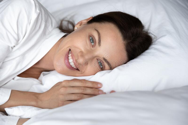 Head shot portrait smiling beautiful woman resting on soft pillow royalty free stock photo