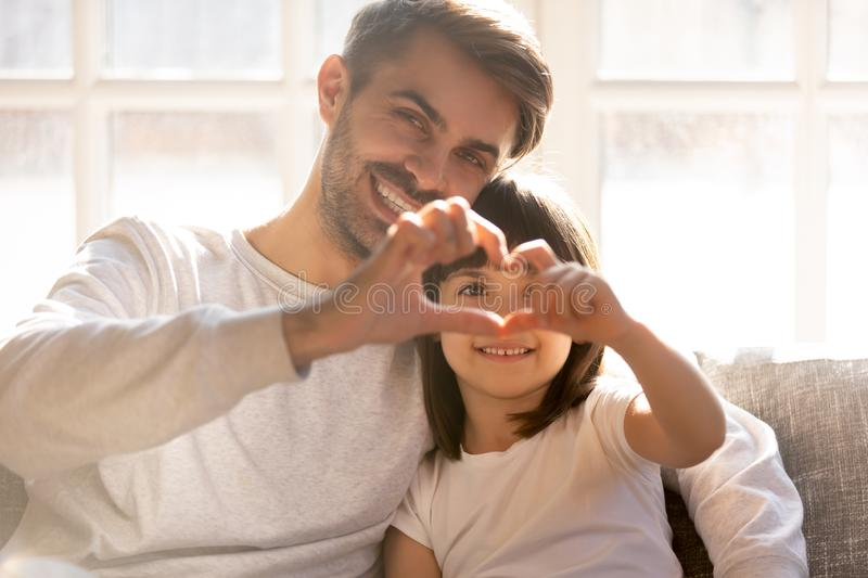 Head shot portrait of smiling father with daughter showing heart stock photos