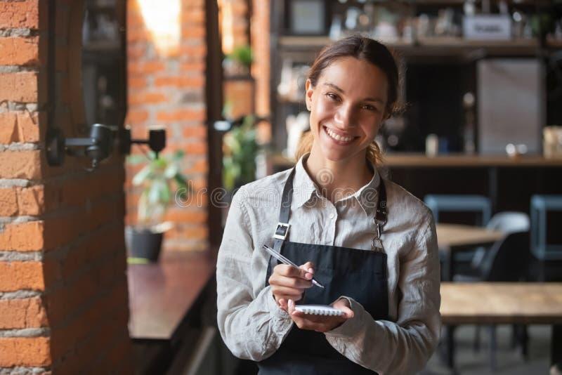 Head shot portrait of smiling waitress ready to take customer order royalty free stock photo