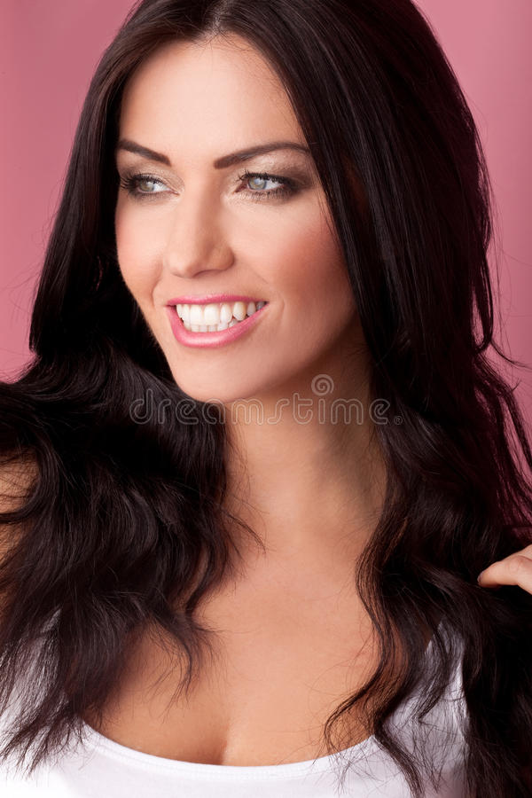 Head shot of a smiling brunette. Looking to her right on a pink background royalty free stock images