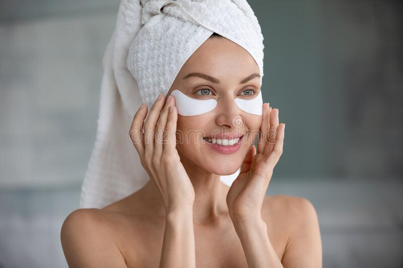 Head shot smiling woman applying hydrogel patches under eyes royalty free stock photos