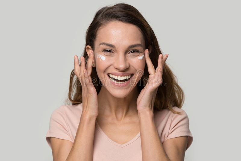 Happy woman looking at camera applying eyelid moisturizing cream stock photography