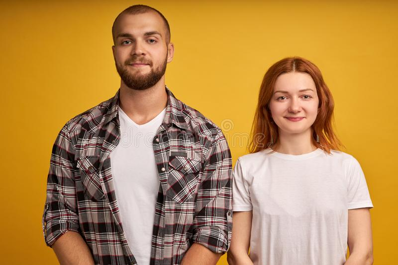 Head shot studio portrait smiling attractive millennial couple in love pose on yellow wall looking at camera, romantic stock photo