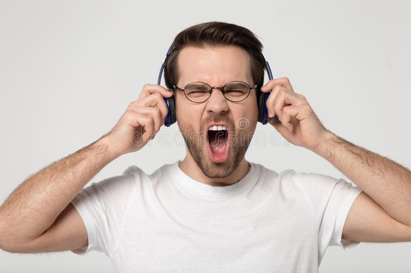 Head shot studio portrait young man enjoying favorite music. stock photos