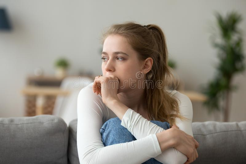 Sad woman sitting on couch alone at home royalty free stock images