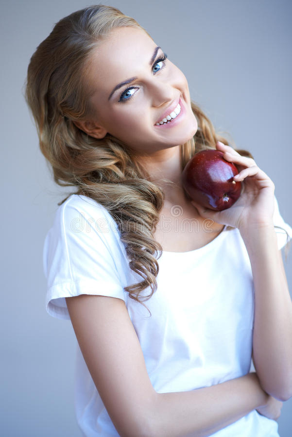 Download Head Shot Of Woman Holding Red Apple Against Grey Stock Photo - Image: 27250164