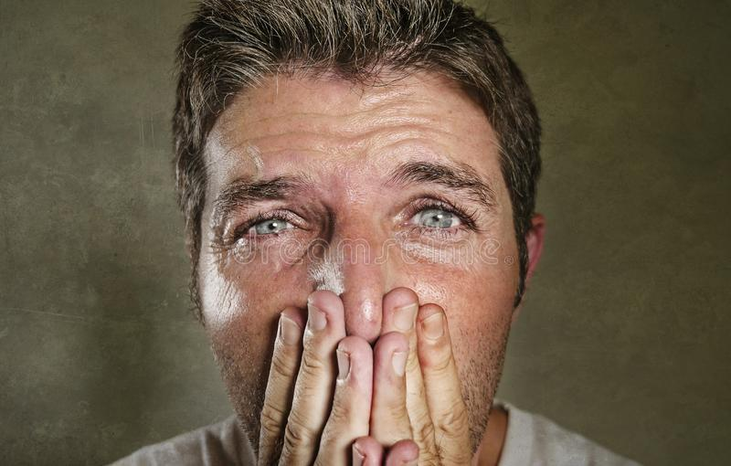Head and shoulders dramatic portrait of young man crying in pain suffering depression and anxiety problem covering his mouth with. The hands feeling sad and stock image