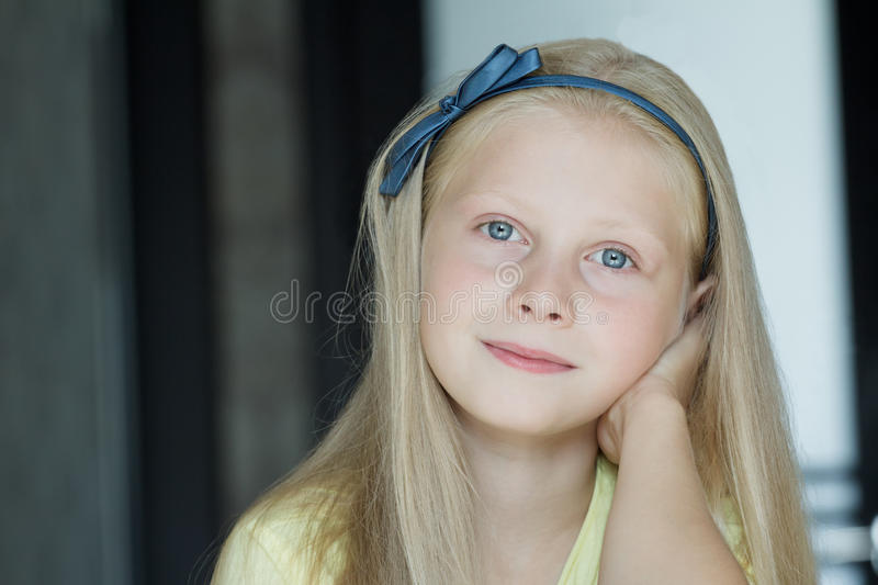 Head and shoulders indoors portrait of teenage girl with blue eyes and fair hair stock photo