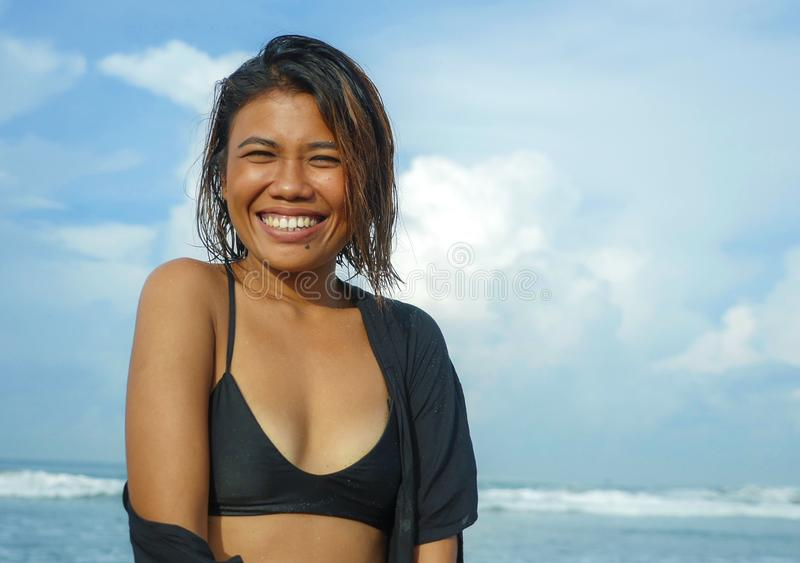 Head and shoulders lifestyle portrait of young beautiful and sexy Asian girl in bikini smiling cheerful enjoying holidays at royalty free stock photo