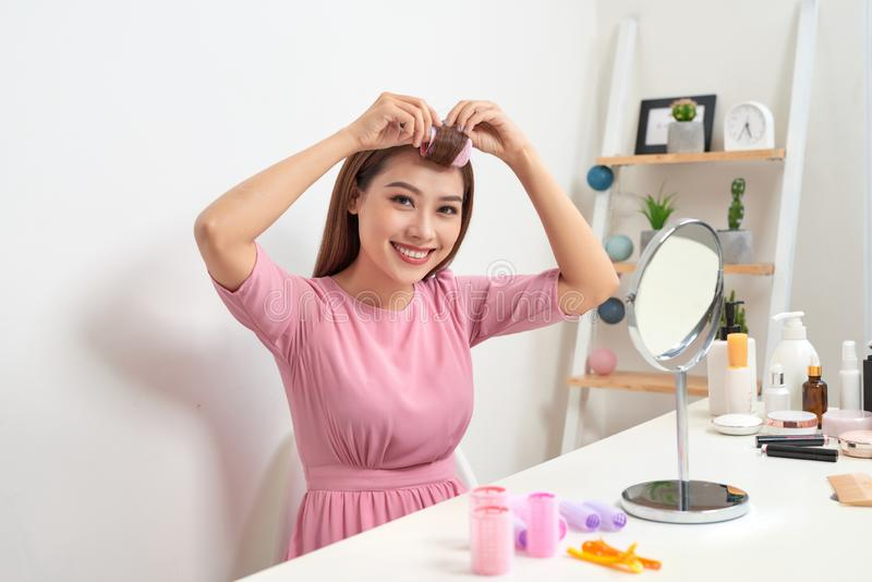 Head and shoulders portrait of beautiful Asian woman wearing hair curlers looking in mirror with wide smile, home interior on royalty free stock photo