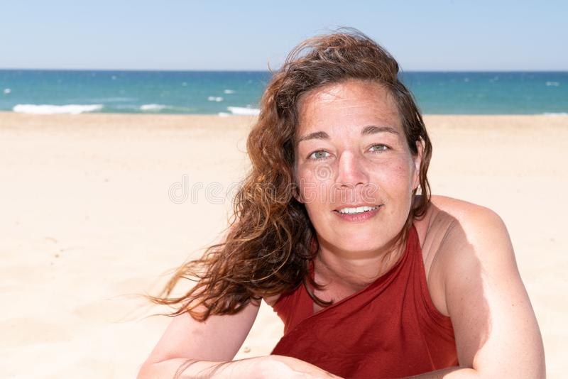 Head and shoulders portrait of happy beautiful middle aged brunette tourist woman in sea beach ocean royalty free stock images