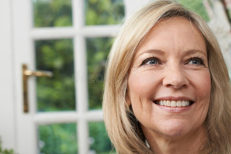 Head And Shoulders Portrait Of Smiling Mature Woman At Home stock photo