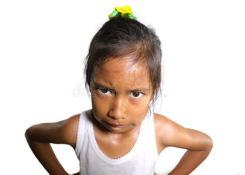 Head and shoulders portrait of sweet upset and disappointed 7 years old Asian girl looking intense to the camera feeling angry and royalty free stock photos