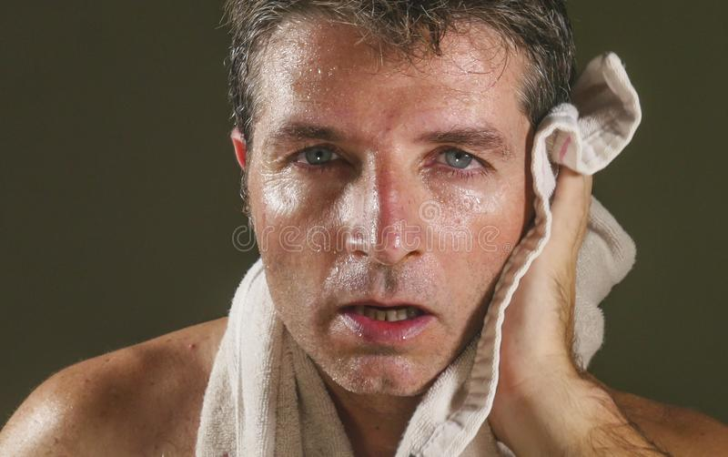 Head and shoulders portrait of young attractive and handsome sport man sweating after gym workout training hard tired and. Exhausted all sweaty drying with stock photography