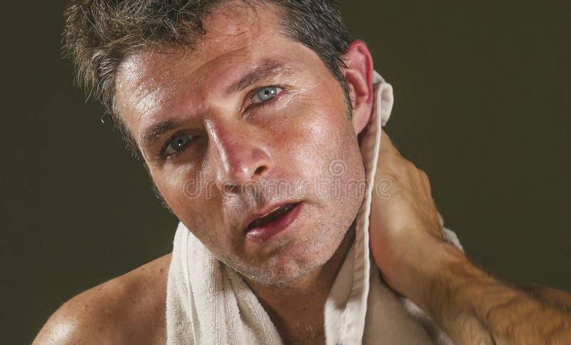 Head and shoulders portrait of young attractive and handsome sport man sweating after gym workout training hard tired and. Exhausted all sweaty drying with stock photo