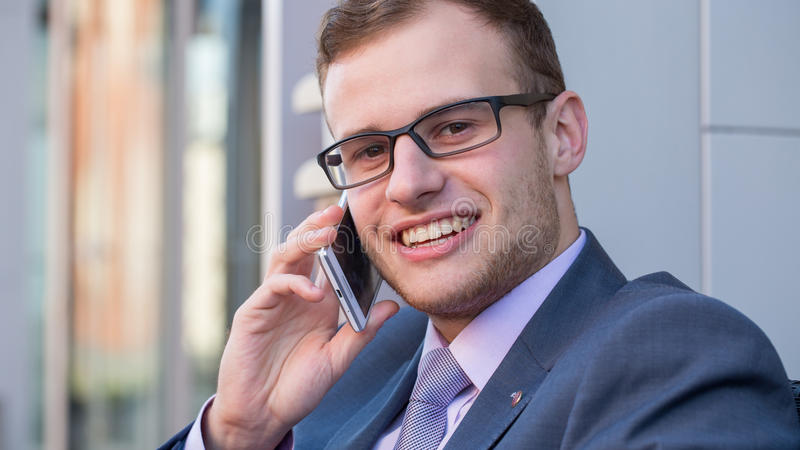 A head and shoulders shot of a 25 year old business man in a suit and shirt with tie and mobile phone. royalty free stock images