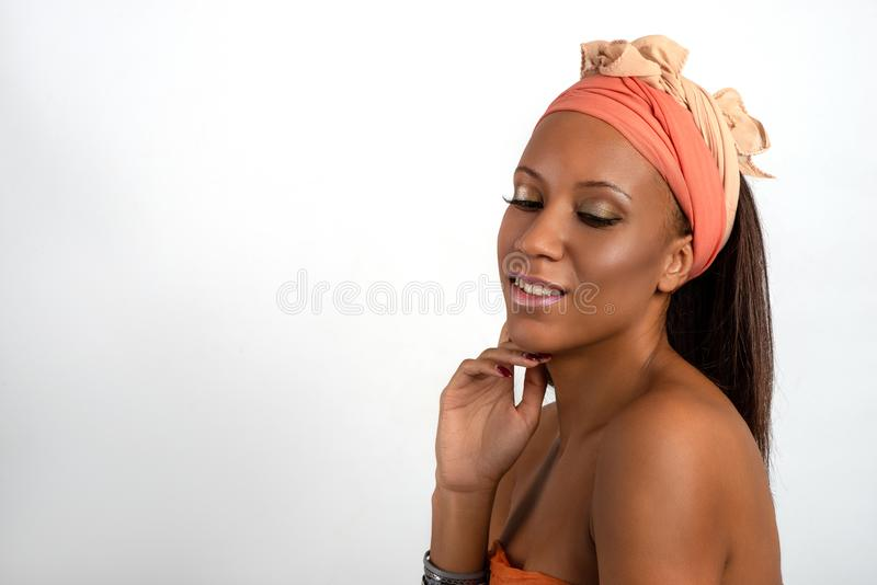 Head and shoulders studio shot of the young woman of the mulatta with make up wearing terracotta bandage on the head royalty free stock photos