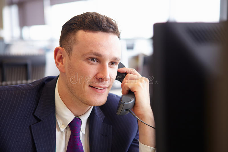 Head and shoulders of a young businessman, using telephone royalty free stock photos