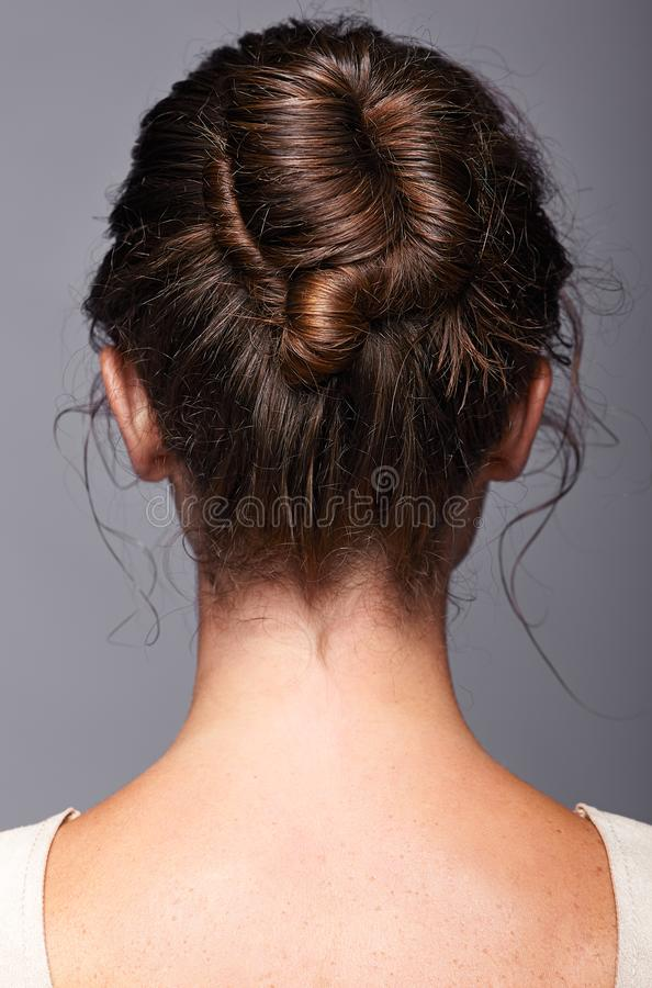 Head and shoulders of a young woman from the back side. Female h royalty free stock photo