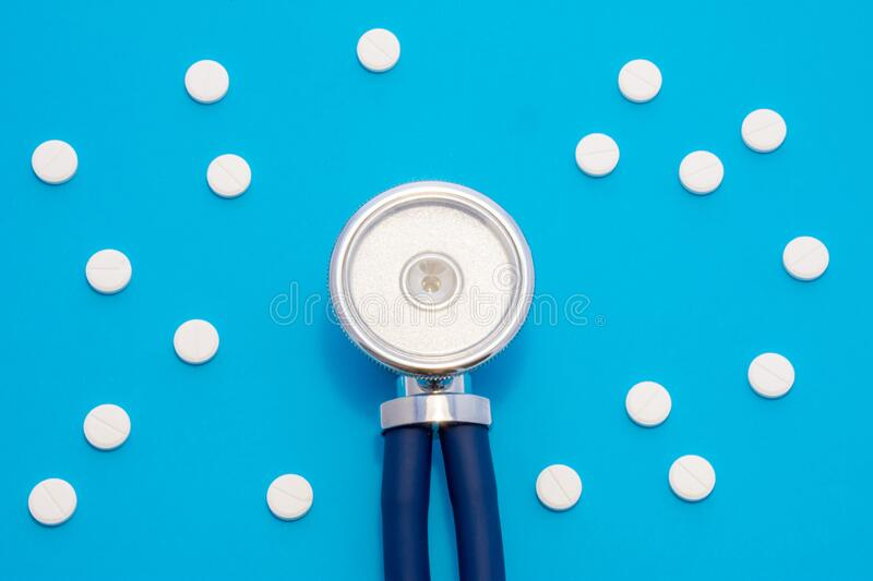 Head of stethoscope is on blue background surrounded by pills or tablets with ornament of polka dots. Concept photo diagnosis, tre royalty free stock images