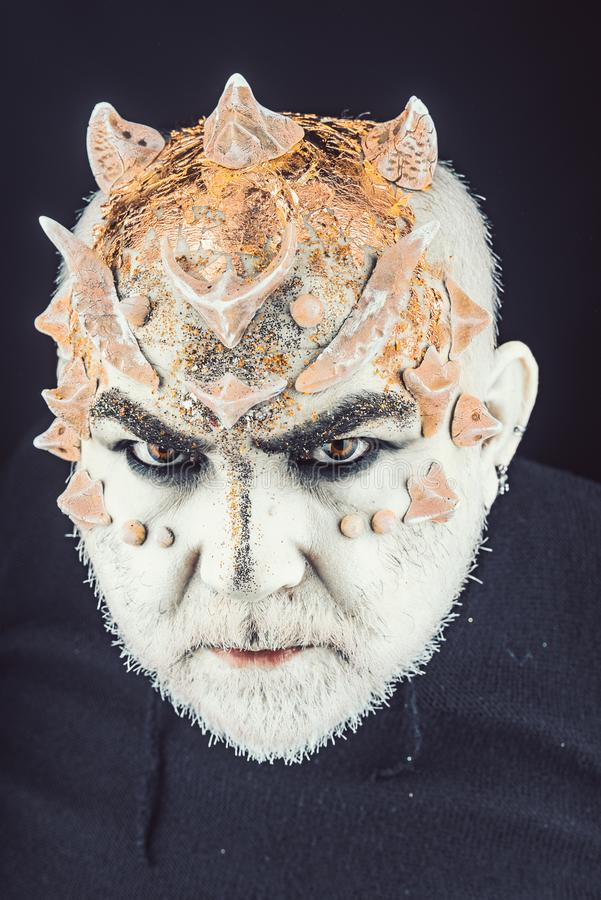 Head with thorns or warts, face covered with glitters, close up. Alien, demon, sorcerer makeup. Fantasy concept. Demon. On serious face, black background royalty free stock image