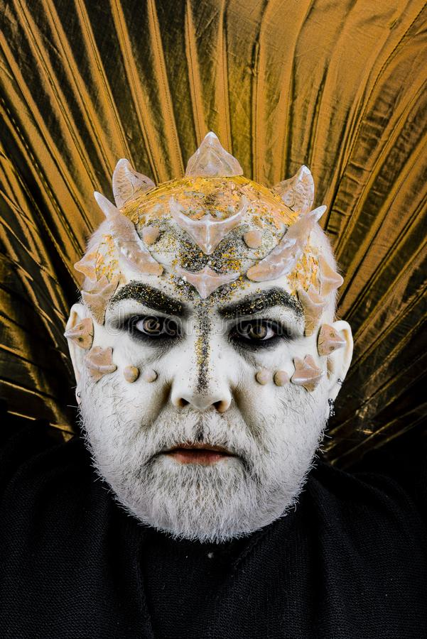 Head with thorns or warts, face covered with glitters, close up. Alien, demon, sorcerer makeup. Senior man with beard stock images