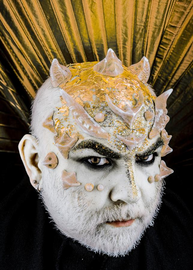 Head with thorns or warts, face covered with glitters, close up. Fantasy concept. Alien, demon, sorcerer makeup. Senior. Man with beard, with monster makeup royalty free stock images