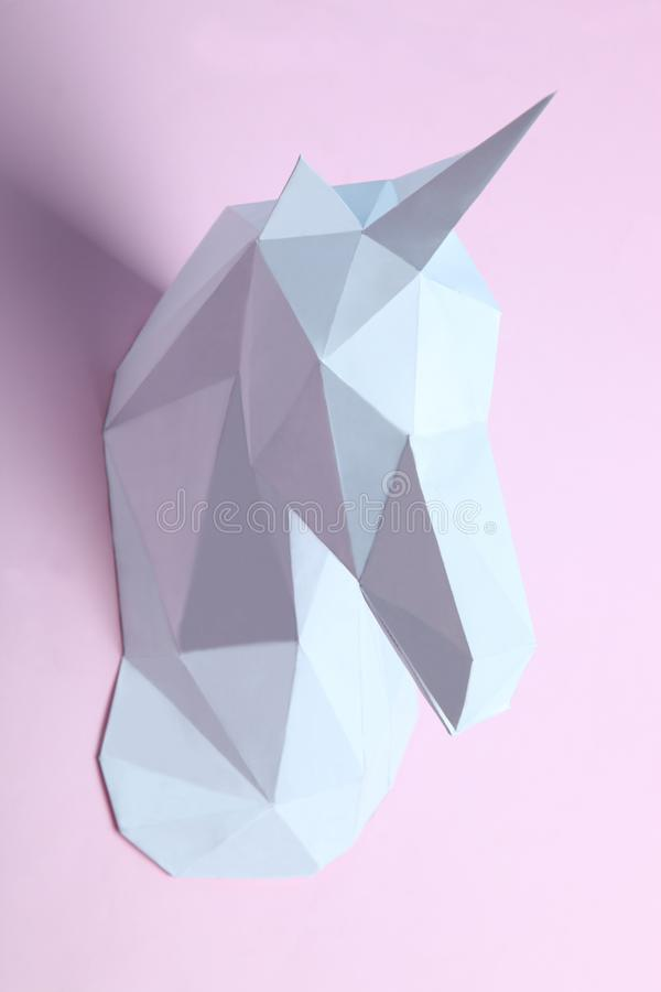 White head of a unicorn. Head of a unicorn of paper on a pink background. Geometry, pastel colors royalty free stock images