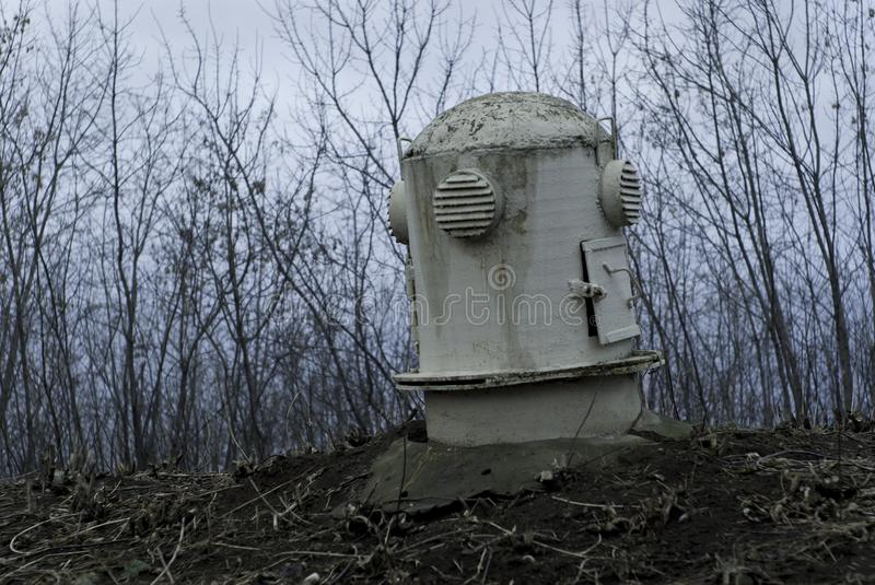 The head of the ventilation shaft of the bomb shelter in a gloomy landscape. The sagging head of the ventilation shaft of an old abandoned bomb shelter in a royalty free stock photo