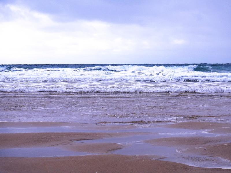 Head on view of the surf and sand at a beach in the South West of the UK stock images