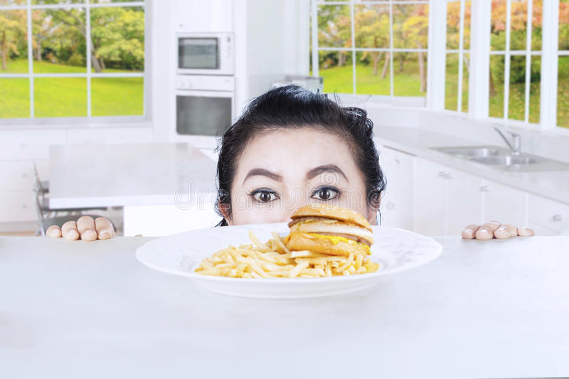 Head of woman with hamburger in the kitchen. Head of young female looking at a hamburger on a plate with autumn background on the window stock photography