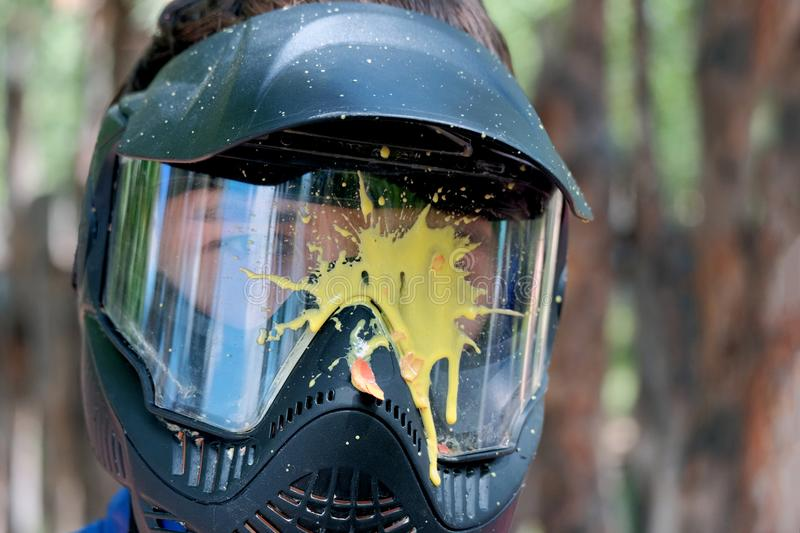 Yellow blot paint on a protective glass mask for playing paintball outside. The head of a young man in a helmet. royalty free stock images