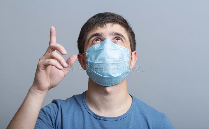 Head of a young man in protective surgical mask looking up and showing by finger up, concept of health and medicine, place for. Advertising clinic services stock images