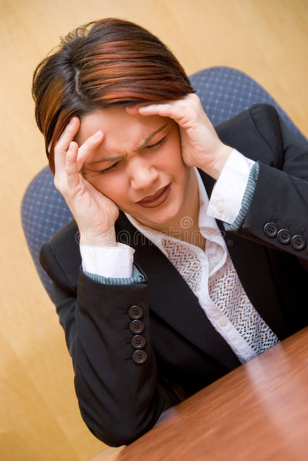 Headache. Burnout woman at her work holding her head royalty free stock image