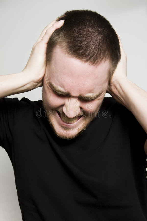 Headache. Young man having very painful headache royalty free stock photography