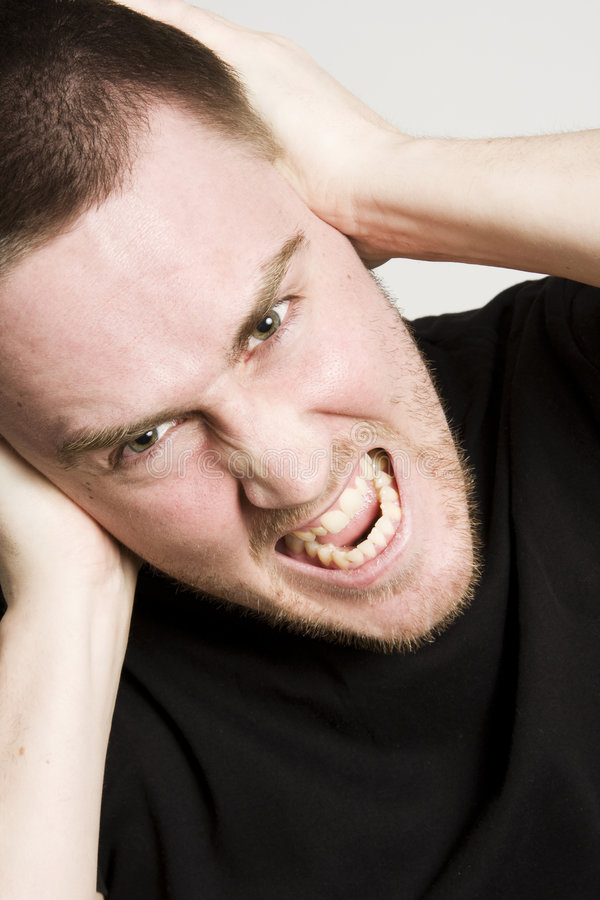 Headache. Young man having very painful headache royalty free stock photos