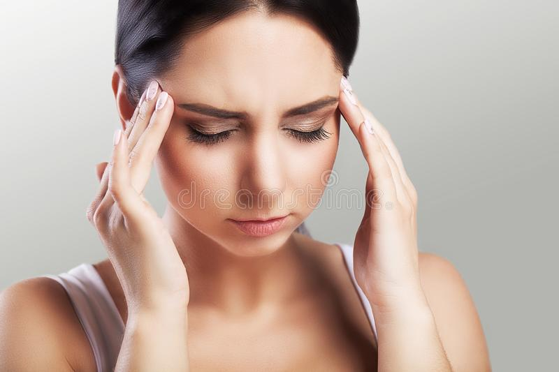 Headache in a beautiful young woman. Fatigue after a working day. Holds a hand in the forehead area. The concept of health. On a g royalty free stock photography
