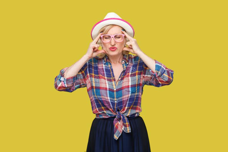 Headache or confusion. Portrait of frowning stylish mature woman in casual style with hat and eyeglasses standing holding her head. With head pain. indoor royalty free stock photography
