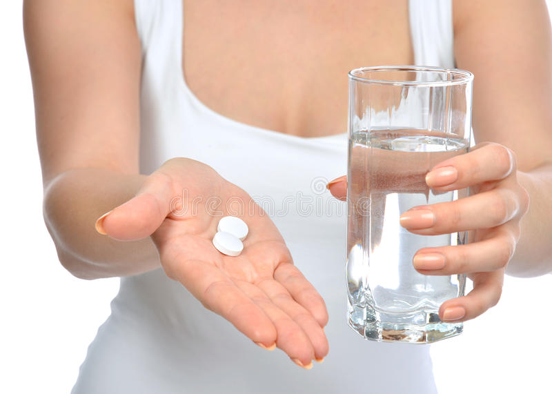 Headache hand with pills medicine tablets and glass of water royalty free stock image