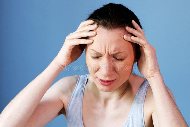 Headache migraine woman work illness flu cold. My head still hurts. Headache and Stress at Work. Young Business Woman Suffering From painful migraine. Exhausted stock photo