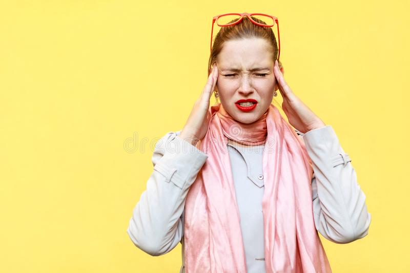 Headache or pain. Distressed woman holding hands on head and cl royalty free stock image