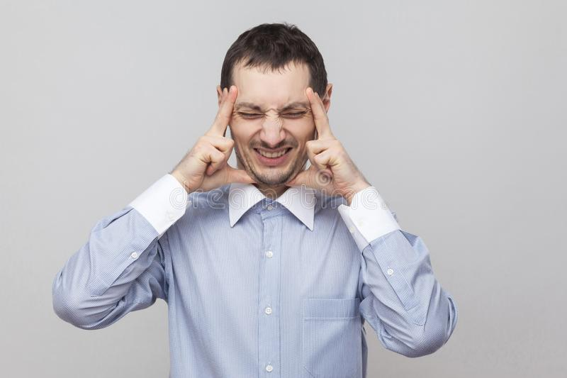 Headache pain. Portrait of angry bristle businessman in classic blue shirt standing holding his painful head, closed eyes and royalty free stock photography