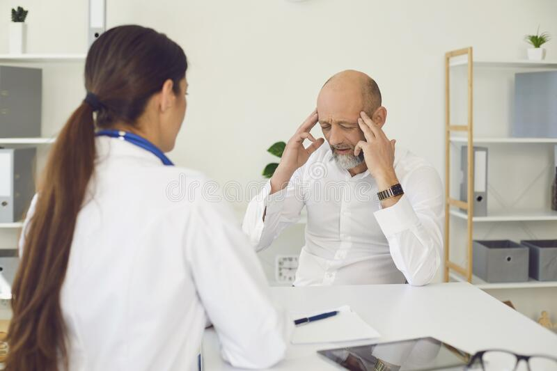 Headache. Patient senor tells the doctor headache symptoms sitting on a chair in a clinic office. royalty free stock photos