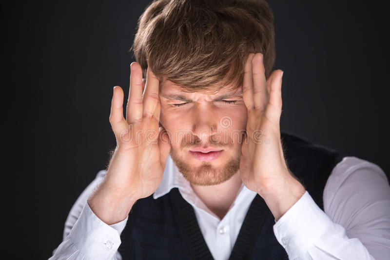 Headache. Tired handsome man with hands over his face. Feeling headache royalty free stock photography