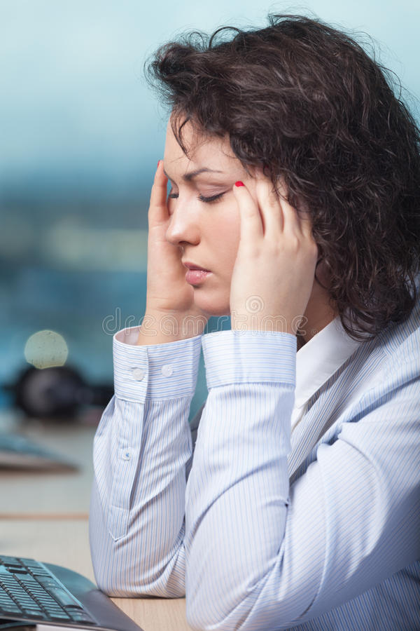 Headache. Woman having head ache at work royalty free stock photo
