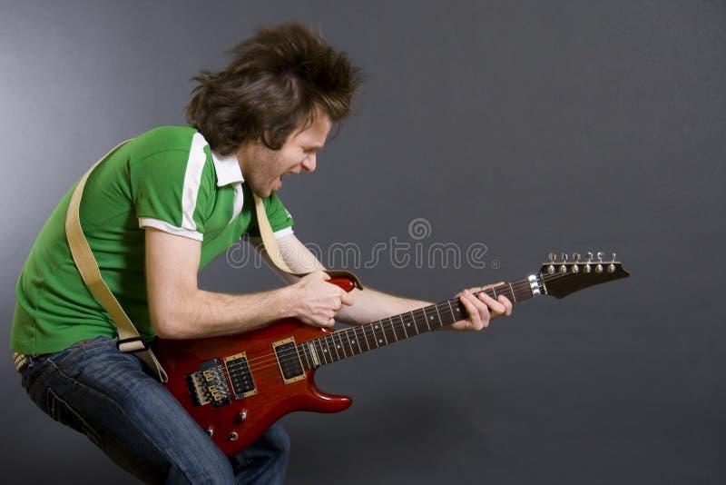 Headbanging Gitarrist, der eine elektrische Gitarre spielt lizenzfreies stockbild