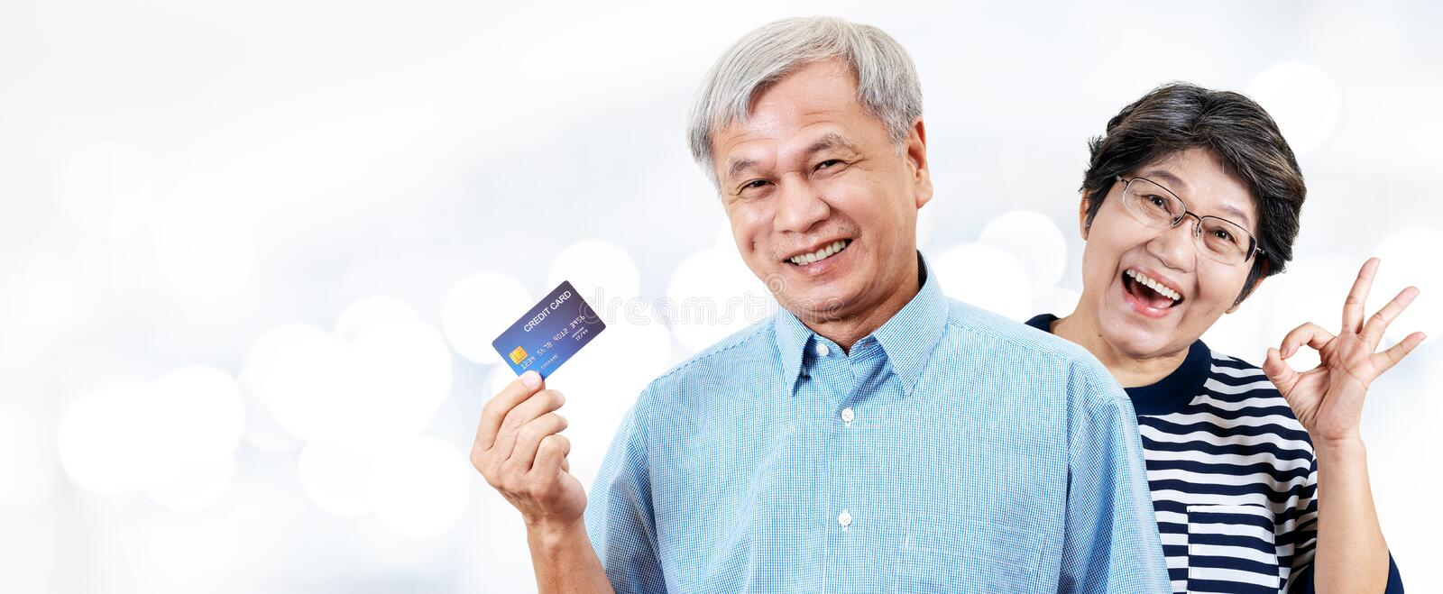 Header of happy asian cheerful senior couple, retirees or older parents smiling and showing credit card with satisfaction in. Elderly consumer shopping stock photography
