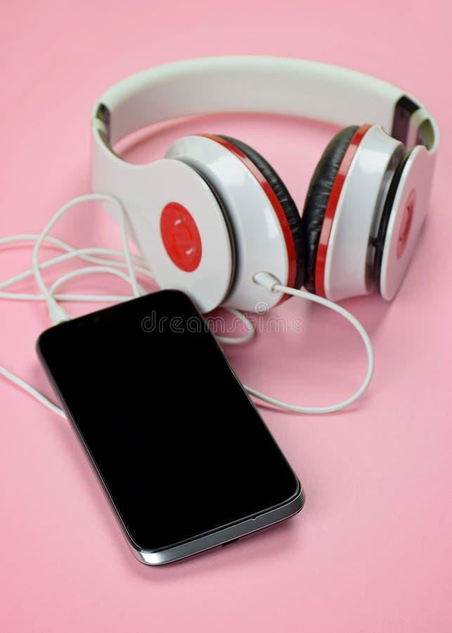 Headfones e smartphone su fondo rosa fotografie stock